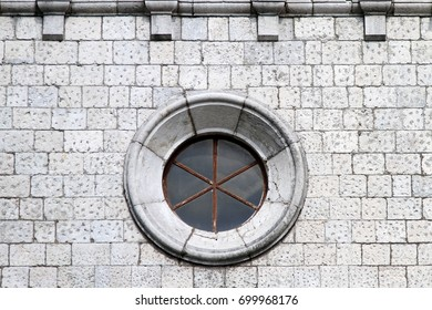 Round window at old stone wall exterior