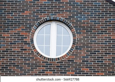 Round window on a beautiful large brick wall.