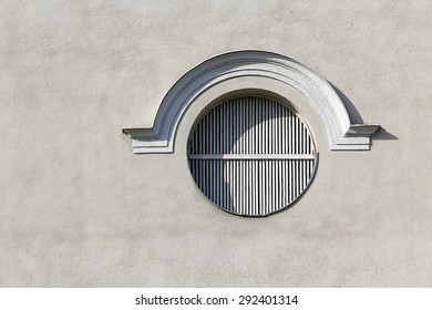 Round window on a blank grey wall