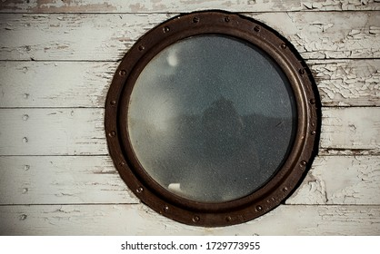 Round window on board the ship. Luke. Old wood texture, white. Reflection in the glass. Metal frame. Detail.