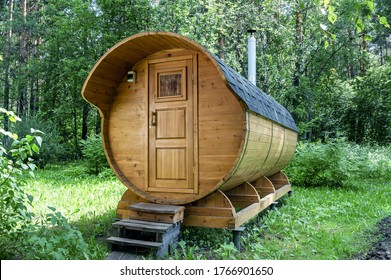 Round wooden barrel bath stands in the forest on a sunny summer day