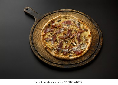 Round wooden board with pizza isolated on a black background.