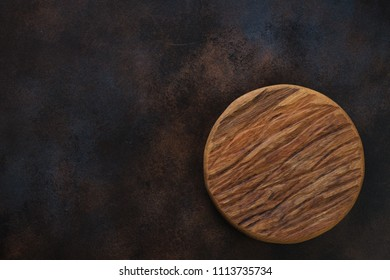 Round wooden chopping board over dark brown metal background, view from above with copy space, horizontal shot