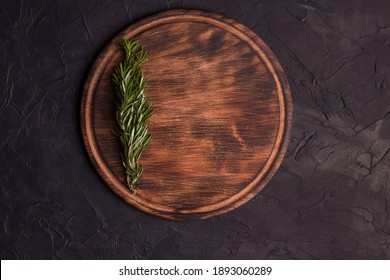 Round wooden cutting board on a black table. Top view of empty kitchen trendy rustic wooden tray