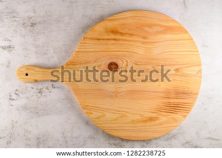 Round wooden cutting board (pizza board) over bright gray stone background. Copy space for text.