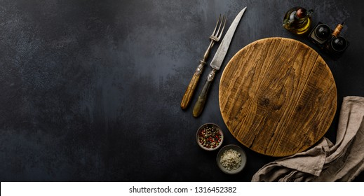 Round wooden Cutting board and Spices for cooking on dark concrete backdrop Surface copy space for design text