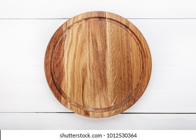 round wooden pizza board on a wooden background, space for text