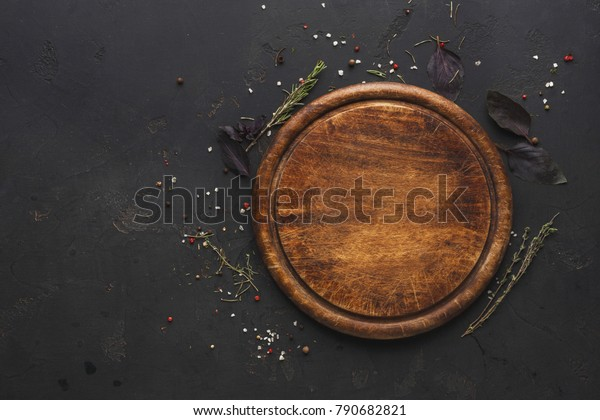 Round wooden plate with herbs and salt on dark wooden background top view