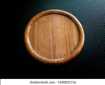 Round wooden plate on a black background