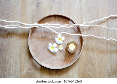 round wooden tray and natural twigs, white beautiful flowers and candle for wallpaper of meditation, mindfulness or zen massage, top view still life