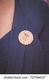 Round wooden wedding boutonniere for the bride's mother wearing navy blue blouse closeup of chest buttonhole