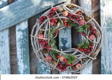 Round wooden wreath of wine with fresh small red apples,rowan, green leaves, cones on the blue fancy background. Wreath on door, outdoor and space. Natural daylight