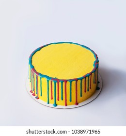 Round yellow birthday cake. Decorative colored stains. Top view. White background. Copy place