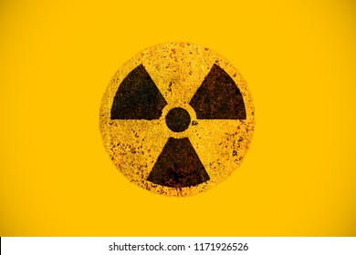 Round yellow and black radioactive hazard (ionizing radiation) nuclear danger warning symbol on rusty metal grungy texture and isolated on yellow background.
