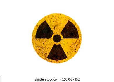 Round yellow and black radioactive (ionizing radiation) nuclear danger symbol on rusty metal grungy texture and isolated on white background.