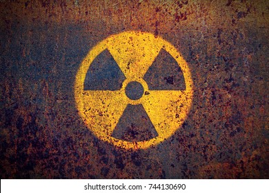 Round yellow and black radioactive (ionizing radiation) danger symbol painted on a massive rusty metal wall with dark rustic grunge texture background.