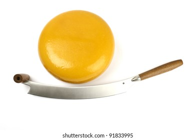 round yellow cheese with cheese knife