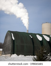 A rounded building with a smoke stack and snow on the ground.