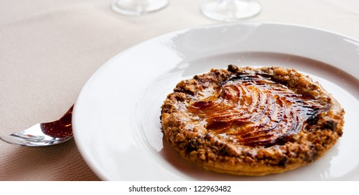 Rounded dessert cake with marmalade on a plate. Idea to use with the culinary arts of fine food and drink, gourmet, or haute cuisine