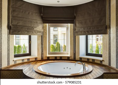 Rounded white bath in stylish interior and beautiful view from window to street. Bath room with elements of ceramic and wood, with big dark brown blinds.