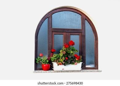 Rounded wood frame  window with red geraniums flower pots and white wall