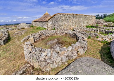 Roundhouse ruins and the reconstructed family nucleus building in Citania de Sanfins. A Castro Village (fortified Celtic-Iberian pre-historic settlement) in Pacos de Ferreira, Portugal.