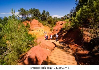 Roussillon, France - June 14, 2018. The Ochre Path le Sentier de Ocres through Red Cliffs of Roussillon Les Ocres, nature park in Vaucluse, Provence