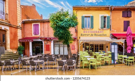 Roussillon, France - October 14, 2016. Colorful buildings painted with locally mined ochre pigment. Couleurs: colors. Brasserie: restaurant serving beer. Presses: squeezed fruit juice. Citron: lemon