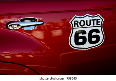 A Route 66 sign on the side of a PT Cruiser.
