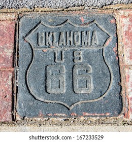 Route 66: US 66 Shield, stamped in concrete, poured between decorative bricks, on the Tulsa sidewalk, Oklahoma