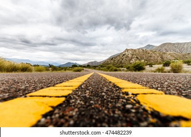 Route between mountains viewed at ground level with cloudy sky in La Rioja, Argentina
