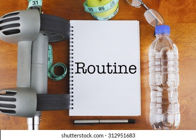 """Routine"" text on notebook with delicious green apple, measure tape, spectacle, a bottle of mineral water, and bodybuilding tools on wooden background - healthy, exercise and diet concept"