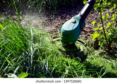 Routine work in the garden, man trimming grass with heavy-duty hand trimmer.