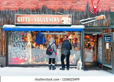 Rovaniemi, Finland - March 2, 2017: Couple in Street Finnish Christmas Market with Winter Saami Souvenirs in Rovaniemi, Finland, Lapland. At the North Arctic Pole.