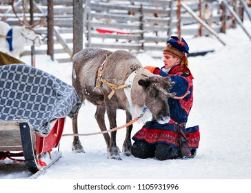 Rovaniemi, Finland - March 3, 2017: Man in Saami traditional costume at Reindeer in Winter Snow Forest at Finnish Farm in Rovaniemi, Finland, Lapland at Christmas. At the North Arctic Pole.