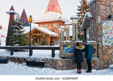 Rovaniemi, Finland - March 5, 2017: Couple at Santa Claus Office in Santa Village with Christmas trees in Lapland, Finland, on Arctic Circle in winter.