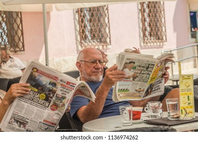 Rovinj, Croatia - May, 2018: Morning time. Beautiful romantic old town of Rovinj. The man in the cafe reads the morning press