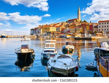 Rovinj, Croatia. Motorboats and boats on water in port of Rovinj. Medieval vintage houses of old town. Yachts landing, high tower of Church of Saint Euphemia. Morning sunrise blue sky withclouds.