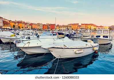Rovinj, Croatia. Motorboats and boats on water in port of Rovinj. Medieval vintage houses of old town. Yachts landing, tower with clock. Morning sunrise blue sky withclouds.