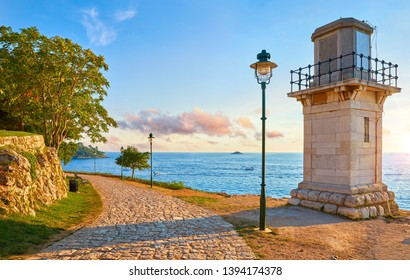 Rovinj, Croatia. Old lighthouse at coast of Adriatic Sea at sunset along street with walkway of paving stones with street lamps. Evening sky with clouds. Summer landscape.