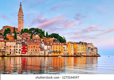 Rovinj Croatia. Sunrise sky above vintage town at Istria peninsula in Adriatic Sea. View from water at old Mediterranean architecture buildings. Coastline and tower of Church of Saint Euphemia.
