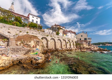 Rovinj, Croatia-16.August 2017., City Rock Beach called ' Baluota ' during the summer season with lots of tourists bathing in crystal clear sea.It is under the town walls and specific for clean sea