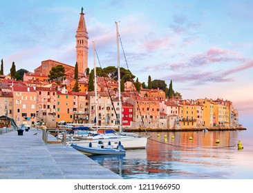 Rovinj, Istria, Croatia. Antique medieval houses and tower of Church of Saint Euphemia. Coastline of Adriatic sea. Sunrise with blue sky and sailing fishing boats on water. Calm silent summer morning.