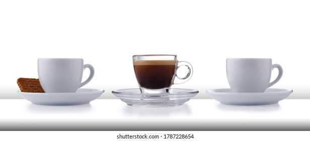 A row of 3 glass and white expresso cups and saucers full of smooth expresso coffee, on a white style bar or table top with a white background