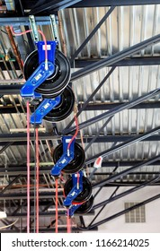 A row of 5 ceiling mounted compressed air hose reels in the repair bays of a car dealership garage.