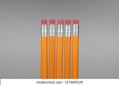 Row of 5 school pencils with pink eraser heads, isolated on a gray background