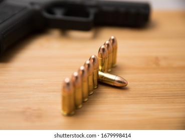 Row of 9mm bullets also showing a gun in the background