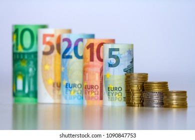 Row of accurately rolled hundred, fifty, twenty, ten and five new paper euro banknotes and pile of metallic coins isolated on white background. Symbol of financial prosperity, wealth and success.