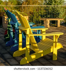 A row of  Adirondack chairs in the evening sun.