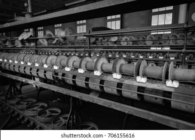 Row after row of spent silk spools sit on antique manufacturing equipment